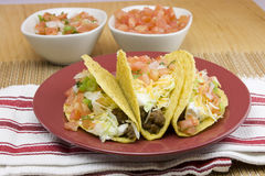 Three crunchy tacos on a red plate Royalty Free Stock Photo