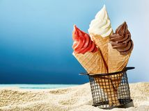 Three crunchy cones with ice cream stuck in sand stock photography