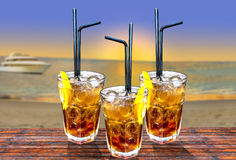 Three Cuba libre exotic tasty cocktail with beautiful sunset and Stock Photography