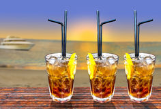 Three Cuba libre exotic tasty cocktail with beautiful sunset and Royalty Free Stock Image
