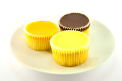 Three Cup Cakes. Three delicious looking cup cakes resting on a white plate on a plain background Stock Photo