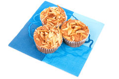Three cup cakes on a blue napkin Stock Images