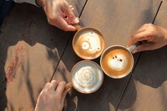 Three cup of different coffee which are cappuccino, mocha and caramel milk holding by hand of friend on the wooden rustic table in stock photo