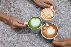 Three cup of different coffee which are cappucino, mocha latte and caramel milk holding by hand of friend on the rustic table royalty free stock photos