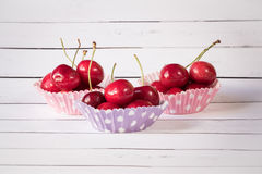 Three cupcake liners with cherries Royalty Free Stock Photography