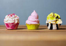 Three cupcakes with blue background Royalty Free Stock Images