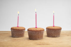 Three cupcakes with candles Stock Photos