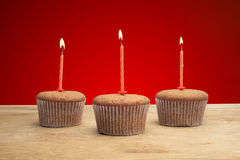 Three cupcakes with candles Stock Photo