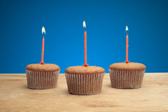 Three cupcakes with candles Royalty Free Stock Photography