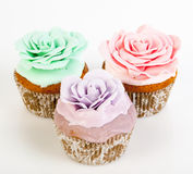 Three cupcakes with colorful sweet roses Stock Photos