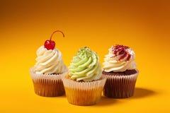 Three cupcakes isolated on orange background Royalty Free Stock Photo
