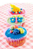 Three cupcakes with marzipan decoration Stock Photo