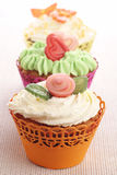 Three cupcakes with marzipan decorations. Stock Images