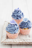 Three cupcakes. Three purple cupcakes with buttercream frosting swirl, silver pearls and edible flowers royalty free stock photos