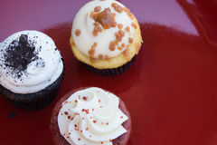 Three cupcakes on a red plate Royalty Free Stock Image