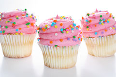 Three cupcakes with sprinkles Royalty Free Stock Photos