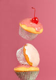 Three cupcakes two on their edges, one floating Royalty Free Stock Photos