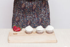 Three cupcakes with white cream on the table Royalty Free Stock Image