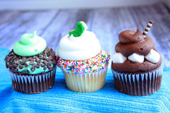 Three cupcakes on a wooden background Royalty Free Stock Photo