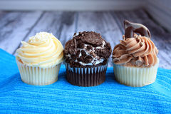 three cupcakes on a wooden background Royalty Free Stock Photography