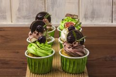 Three cupcakes on a wooden board. Wooden background. A delicious dessert. Royalty Free Stock Photo