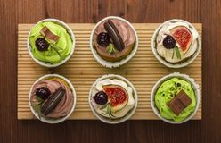 Three cupcakes on a wooden board. Wooden background. A delicious dessert. Royalty Free Stock Image