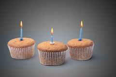 Three cupcakes on a wooden table Royalty Free Stock Photo