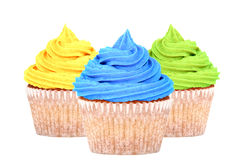Three cupcakes with yellow, blue and green icing Stock Image