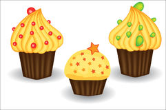 Three cupcakes with yellow cream, berries and powders. Sweet, dessert Royalty Free Stock Image