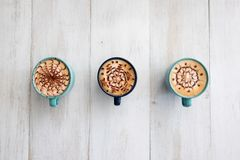 Three cups of coffee symmetrically arranged and ready to share stock image