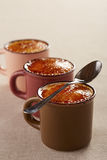 Three cups of creme brulee Stock Images
