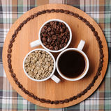 Three cups with different stages of coffee: green and roasted beans and espresso. On wooden board. On plaid texture. Three cups with different stages of coffee Royalty Free Stock Image