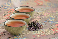 Three cups filled with tea on a beautiful tablecloth. And a pinch of fragrant flower tea Stock Photos