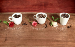 Three cups  full of coffee beans with roses. Stock Photo