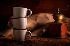 Three cups full of coffee beans on wooden table stock photo