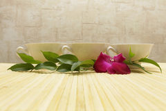 Three cups and green leaves. Three cups of tea, green leaves and orchid on beige background Stock Photo
