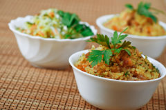 Three cups of pilaf on bamboo table Royalty Free Stock Image