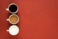 Three cups on red background Royalty Free Stock Photos