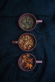 Three cups of spices on the black background. Three cups of spices on the black textile Stock Photography