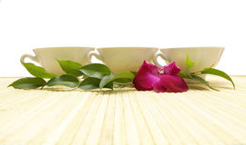 Three cups of tea. Green leaves and orchid Royalty Free Stock Image