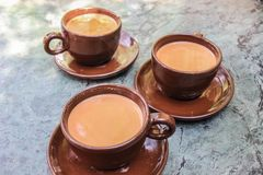 Three cups of traditional Nepalese tea with milk and spices in brown ceramic cups stock photography