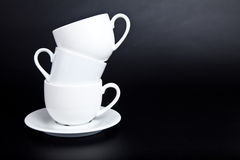 Three cups of white on a black Stock Photography