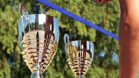 Three cups for the winners of the tournament. Action on the beach. Three  cups for the winners of the tournament beach volleyball stock footage
