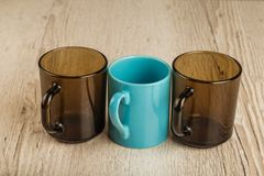 Three cups on a wooden background in different positions. Three cups on a wooden background in different positions stock photography