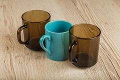 Three cups on a wooden background in different positions. Three cups on a wooden background in different positions stock image