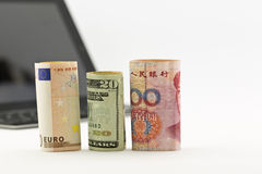 Three currencies intent on technology business. Three currencies, euro, United States dollar, and Chinese yuan, placed before tablet and keyboard stock photos