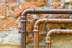 Three curving pipes on a brick wall Stock Photography