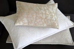Three cushions. Three textured stylish cushions on a grey sofa stock image