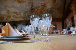 Three cut-glass gobles stand on dinner table. Three cut-glass gobles stand on big dinner table near knives and plates with placemats Stock Images