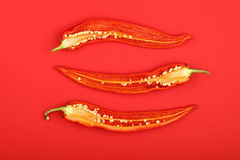 Three cut hot chili peppers on red background Royalty Free Stock Photography